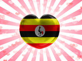Uganda flag painted on glass heart on stripped background — Stock Photo