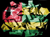 Togo flag painted on pieces of torn paper on black background — Stock fotografie