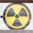 Stock Photo: Nuclear radiation symbol painted on painted over wooden board