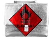 Highly flammable sign drawn on painted on small briefcaseor leather handbag — Stock Photo