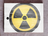 Nuclear radiation symbol painted on painted over wooden board — Stock Photo