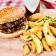 Burger with idaho potatoes on wooden board — Stock Photo