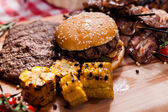 Set of grilled meat and burger on wooden board — Stock Photo