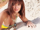 Beautiful woman lying down on a beach — Stok fotoğraf