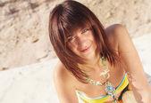 Beautiful woman lying down on a beach — ストック写真