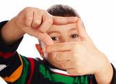 Chlapec při pohledu skrz prst rám — Stock fotografie