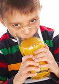 Chlapec pít pomerančový džus — Stock fotografie