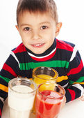 Boy holding a tomato, orange juices and milk — Stock Photo