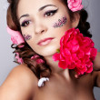 Girl with a beautiful visage and flowers in her hair — ストック写真