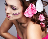 Girl with a beautiful visage and flowers in her hair — Stock Photo