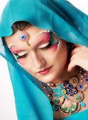 Chica con un rostro hermoso y joyería hecha a mano — Foto de Stock