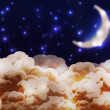 Night cartoon style sky with clouds, stars and half moon — Image vectorielle