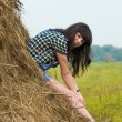 Portrait of pretty brunette lying on haystack — Stock Photo