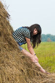 Portrait of pretty brunette lying on haystack — Stock Photo