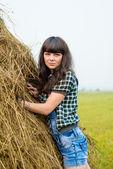 Portrait of pretty brunette standing near the haystack — Stock Photo