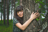 Portrait of beautiful girl hugging birch in the forest — Stock Photo