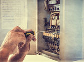 Electrician works on equipment, retro styled — Stock Photo