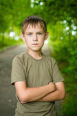 Close-up portrait of serious little boy with folded hands outdoo — Stock Photo
