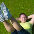 Happy young woman doing exercise on green grass — Stock Photo