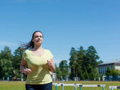 Young woman jogging at the stadium — Stock Photo