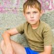 Close-up portrait of serious little boy sitting outdoors — Stock Photo