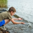 Close-up portrait of serious little boy sitting near the river — Stock Photo
