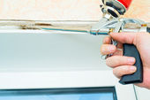Nail gun being used to install trim around window — Stock Photo