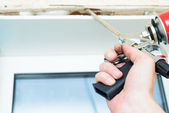 Nail gun being used to install trim around window — Stock Photo