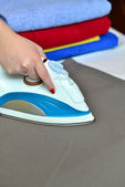 Close-up of woman's hand ironing clothes on the table against th — Stockfoto