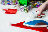 Close-up of woman's hand ironing the christmas hat on the backgr — Stock Photo