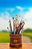 Art brushes in a vase against the indistinct nature — Stock Photo