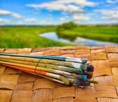 Paint brushe on the surface of the wicker on background summer l — Stock Photo
