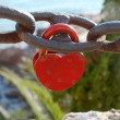 Stock Photo: Padlocks in the form of red heart shape on a chain rusted steel