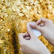 Close up of buddhist's hand placing gold leaf on buddha statue — Stock Photo