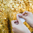 Stock Photo: Close up of buddhist's hand placing gold leaf on buddhstatue