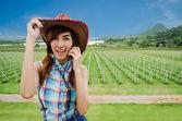 Asian women wear blue plaid shirt against green field — Stock Photo