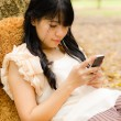Asian girl playing cell phone — Stock Photo