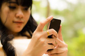 Asian girl playing cell phone — Stockfoto