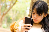 Asian girl playing cell phone — Stock fotografie