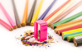 Pink sharpener arounded with pencil — Stock Photo
