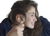 A young girl with a magnifying glass next to her ear — Foto Stock