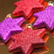 Colored christmas stars, supported gold background — Stock Photo