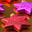 Stock Photo: Colored christmas stars, supported gold background