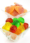 Transparent jelly beans, gummy hearts in the background — Stock Photo