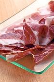 "Slices of Iberian ham ""of acorn"" on glass tray — Stock Photo"