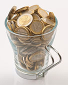 Teacup full of coins of one and two euro — Stockfoto