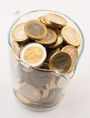 Glass jar full of coins of one and two euro — Stock Photo