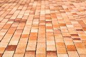Red cobblestone sidewalk blurred degraded — Stock Photo