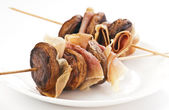 Skewers of mushrooms and bacon on white plate — Stock Photo