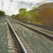 Stock Photo: Bright train tracks moving away